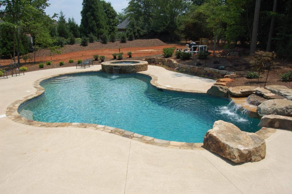 Located in Greenville, SC, is a Lagoon gunite pool with a raised spa. It features rock coping, stacked rock waterfall, Caribbean Blue Pebble Tec, and Kahlua Crème Spray Deck.