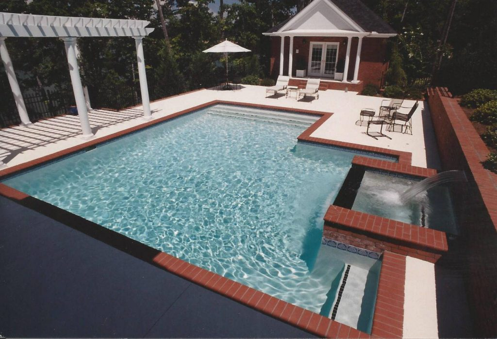 Located in Seneca, SC, is a Freeform gunite pool with a raised spa and a sheer descent waterfall. It features Blue Quartz Diamond Brite finish, brick coping, and Ivory Spray Deck.