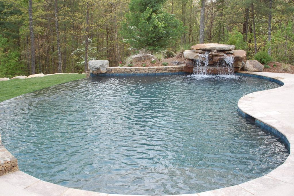 Located in Seneca, SC, is a Freeform gunite pool with an infinity edge. It features Silver Travertine coping, a stacked rock waterfall, and a Midnight Blue Pebble Tec finish.