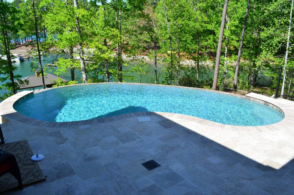 Located in Seneca, SC, is a Freeform gunite pool with an infinity edge. It features Silver Travertine coping and pavers.