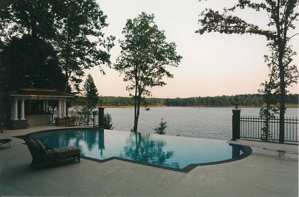 Located in Hodges, SC, is a Roman End Gunite Pool with an Infinity Edge. It features brick coping, Caribbean Blue Pebble Tec, and a Kahlua Crème Spray Deck.