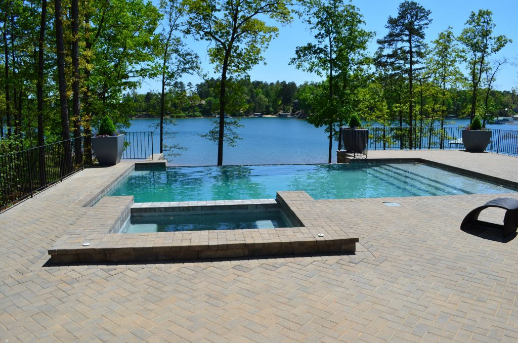 Located in Seneca, SC, is a rectangular gunite pool with an infinity edge and an attached spa. It features brick coping, brick pavers, and a Caribbean Blue Pebble Tec.