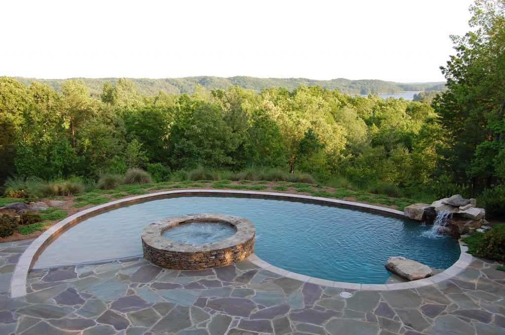 Located in Seneca, SC, is a Kidney gunite pool with a raised spa. It features a stacked rock waterfall, Silver Travertine coping, Flagstone pavers, zero entry, an in floor cleaning system, and Caribbean Blue Pebble Tec.