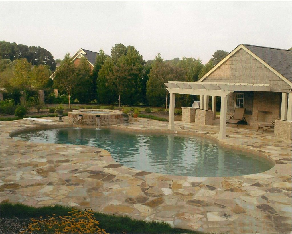 Located in Easley, SC, is a Lagoon gunite pool with a raised spa. It features two waterfalls, Flagstone pavers, and Sandy Beach Pebble Tec.