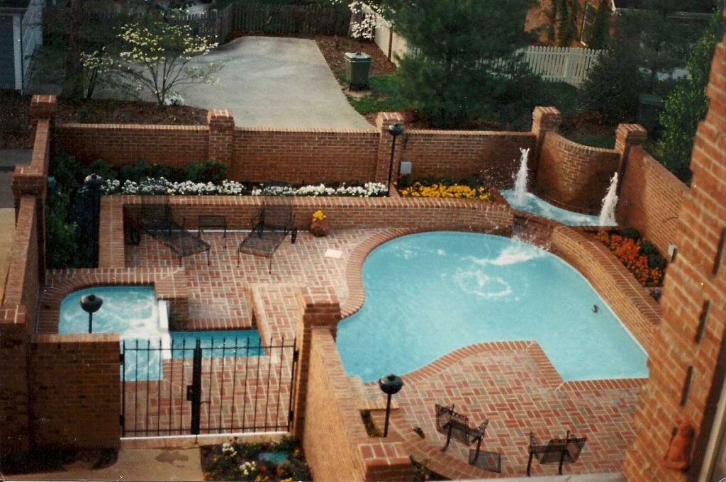 Located in Greer, SC, is a Freeform gunite pool with a raised spa. It features brick coping and pavers and 2 bubblers.