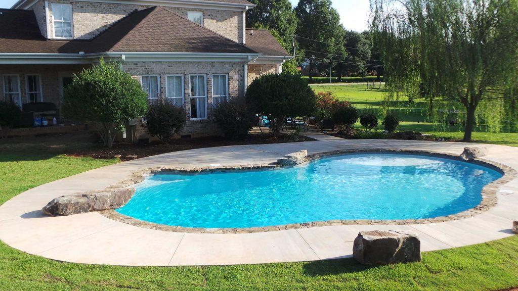 Located in Piedmont, SC, is a Lagoon gunite pool with a tanning ledge. It features a jump rock, swim out, rock coping, and Super Blue Diamond Brite.