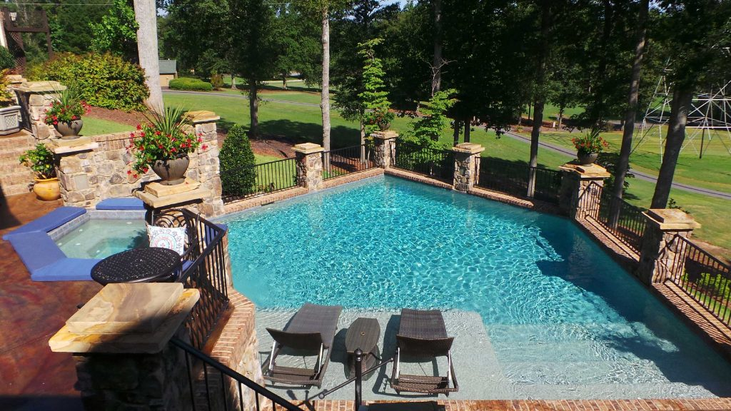 Located in Easley, SC, is a Freeform gunite pool with a raised spa and tanning ledge. It features brick coping, an acid stain on the deck, and Blue Lagoon Pebble Tec.
