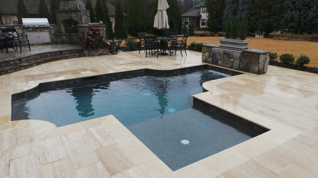 Freeform gunite pool with a tanning ledge. It features a 4 foot sheer descent with a rock planter, Silver Travertine coping and pavers, and Tahoe Blue Pebble Tec.