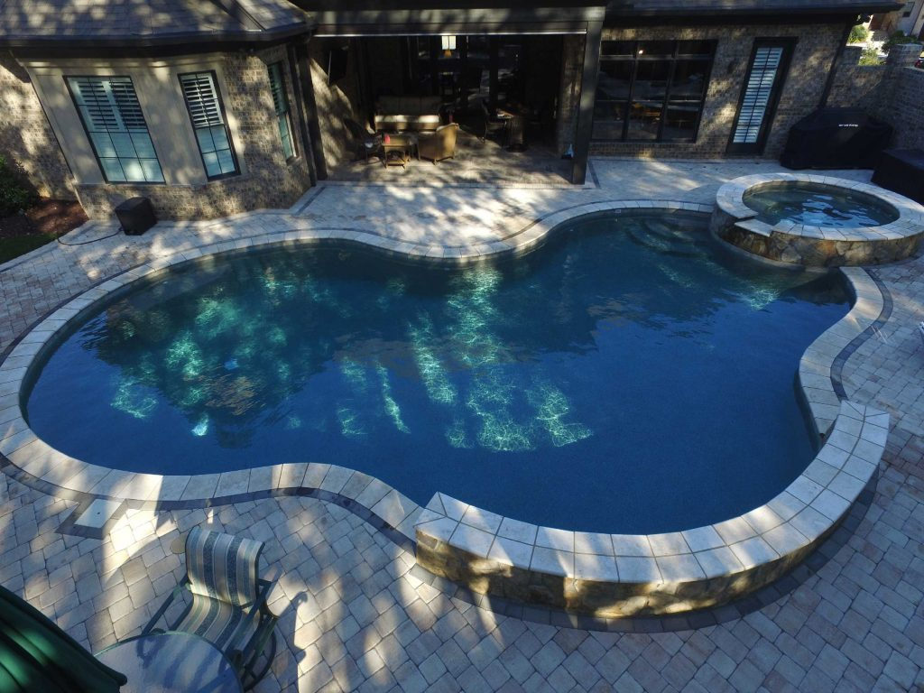 Located in Greenville, SC, is a Lagoon gunite pool with a raised spa. It features concrete pavers, Silver Travertine coping, and Caribbean Blue Pebble Tec.