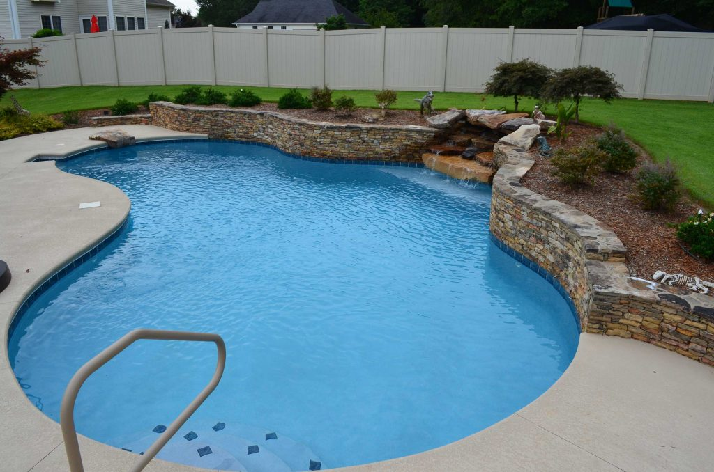 Located in Easley, SC, is a Lagoon gunite pool. It features a stacked rock waterfall and retaining wall, a diving rock, Aqua Blue Diamond Brite, and Kahlua Crème Spray Deck.