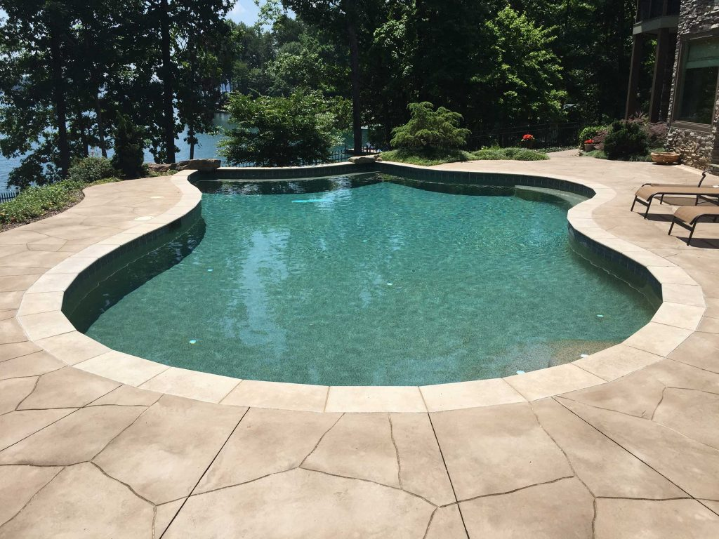 Located in Seneca, SC, is a Freeform gunite pool with multiple benches, featuring Travertine coping, stamped concrete deck, and an in floor cleaning system.""