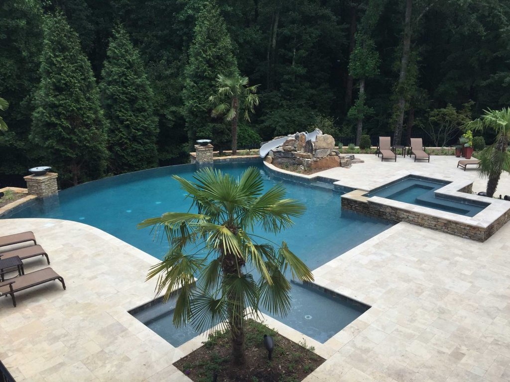 Located in Greer, SC, is a Freeform gunite pool with a stacked rock spa. It features a vanishing edge, fire bowls, a slide, Silver Travertine coping and pavers, an in-floor cleaning system, and French Grey Pebble Sheen