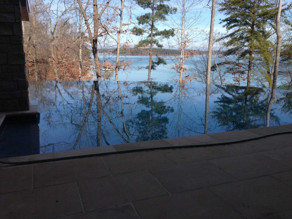 Located in Seneca, SC, is a Freeform gunite pool with a vanishing edge. It features an in-floor cleaning system, Blue Stone coping and pavers, and Aqua Blue Pebble Sheen.