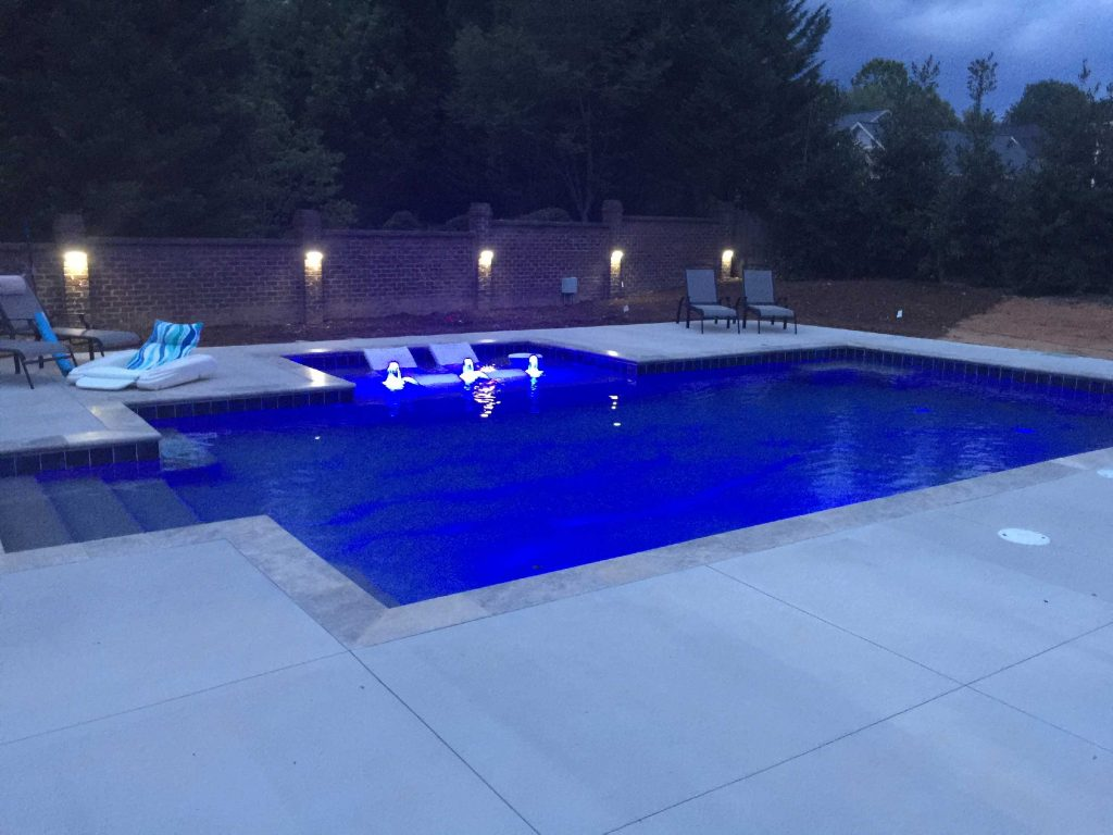 Located in Greer, SC, is a rectangular gunite pool with a tanning ledge. It features 3 bubblers, Silver Travertine coping, and Kahlua Crème Spray Deck.
