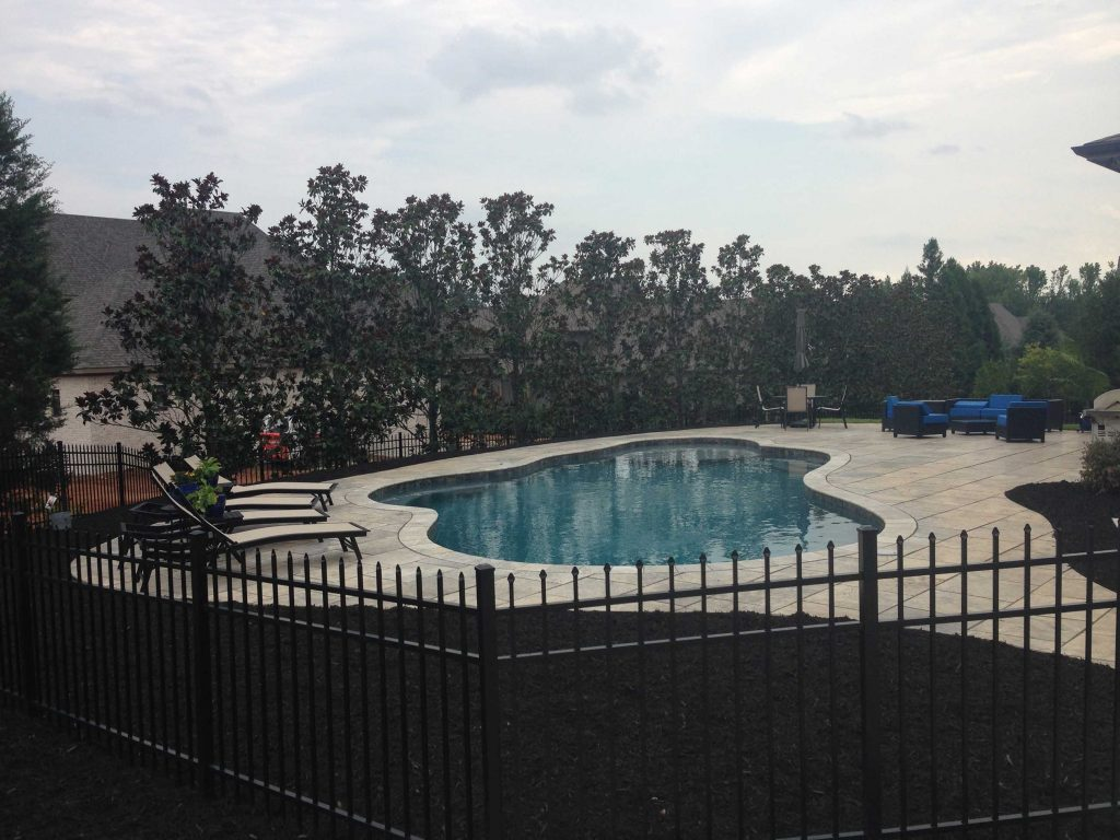 Located in Simpsonville, SC, is a Lagoon gunite pool with a tanning ledge. It features Silver Travertine coping and pavers and Caribbean Blue Pebble Tec.