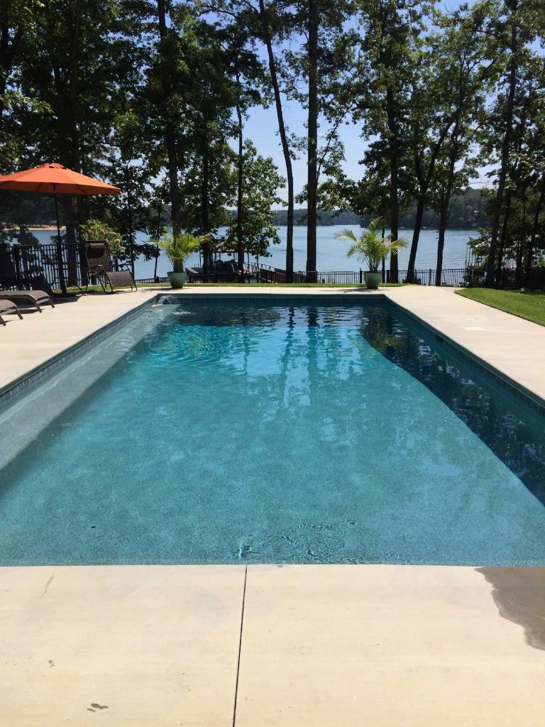 Located in Seneca, SC, is a rectangular gunite pool with a bench and Aqua Blue Pebble Sheen.