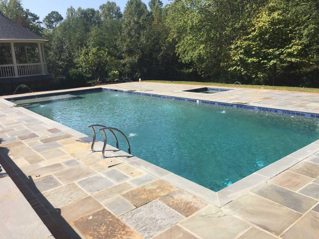 Located in Greenville, SC, is a rectangular gunite pool with an in-ground spa. It features a Badu Jet swim resistance system, 3 deck jets, a tanning ledge, Blue Stone coping and pavers, and Caribbean Blue Pebble Tec.