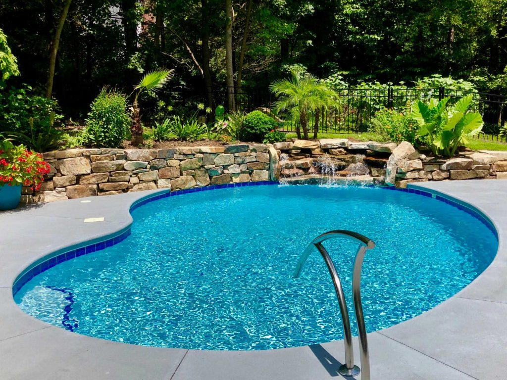 Located in Seneca, SC, is a Kidney gunite pool with a bench seat. It features a stacked rock waterfall, Gun Metal Spray Deck, and Blue Quartz Diamond Brite.