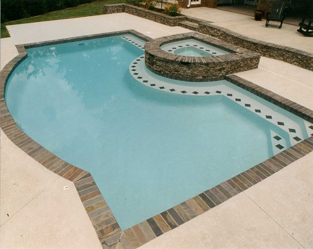 Located in Greenville, SC, is a Freeform gunite pool with a stacked rock spa. It features a bench seat, brick coping, and Desert Sand Spray Deck.
