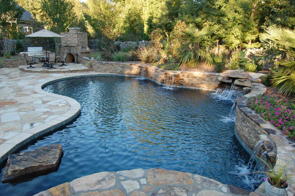 Is a Freeform gunite pool with a stacked rock wall. It features 4 waterfalls, a stacked rock waterfall, an outdoor kitchen, Silver Travertine coping, Flagstone pavers, and Tahoe Blue Pebble Tec.