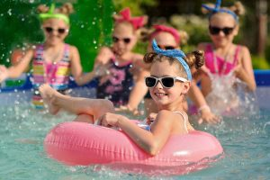 kid on float with sunglasses
